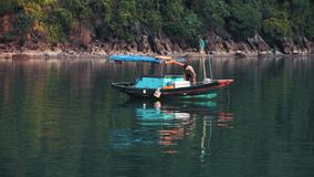 A small boat prepares supplies to sell to passing cruise ships at Ha Long Bay stock video footage
