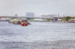 Small boat pulling commercial barge on chao phraya river Stock Images