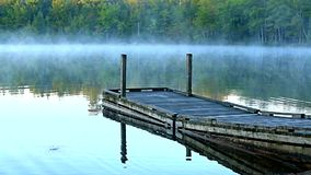 Small boat ramp dock rocking in the early morning light. stock footage