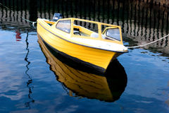 Small boat reflecting on sea. Small yellow wooden boat moored by wharf and reflecting on blue sea stock photography