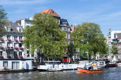 Small boat with relaxing people in Amsterdam canal Stock Images