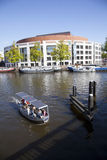Small boat in river amstel in front of opera house Royalty Free Stock Images