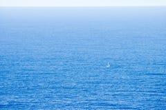Sailing in the ocean. Small boat sailing in the atlantic ocean, minimalistick shot Royalty Free Stock Image