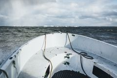 A small boat sailing in baltic sea with Paldiski, Estonia port in background. stock images