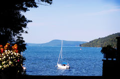Small boat sailing in bay out to the ocean. Royalty Free Stock Images