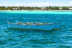 Small boat sailing on the big turquoise ocean with waves. Stock Photography
