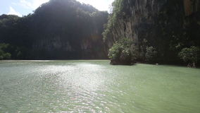 Small boat sailing in the lagoon among the rocks stock video footage