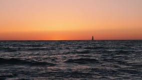 Small boat sailing in sea against beautiful sunset. Sea sundown with sailboat on horizon.  stock footage