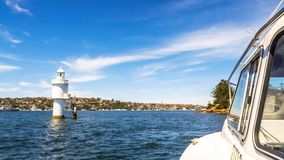 Small boat sails pass shark Island Light, an active pile lighthouse located just north of Shark Island. An island in Sydney Harbour, New South Wales, Australia stock photos