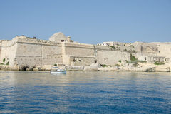 A small boat sails past the walls of the ancient city Stock Photo