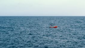 Small boat sails on sea. To meet waves stock video