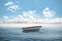 Small boat in the sea with city on horizon Stock Photo