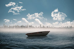 Small boat in the sea with city on horizon Royalty Free Stock Images