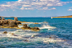 Small boat in the sea near rocky shore. Small boat sails at distance in the sea. waves break on the huge boulders  on the rocky shore. on the other side of of Stock Images