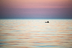 Small boat in the sea at sunrise Stock Photo