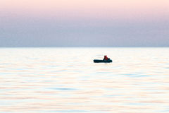 Small boat in the sea at sunrise stock image