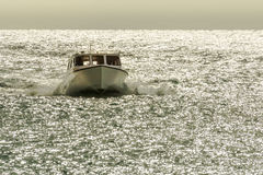 A small boat speeds through the glistening ocean water. A small boat speeds through the glistening ocean water as it approaches a small island that is part of Royalty Free Stock Images