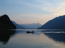 Small boat on still waters of Brienzersee, Switzerland at sunset Royalty Free Stock Images