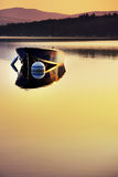 Small boat in sunrise light. Small boat moored on a still dawn lake Royalty Free Stock Photos