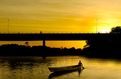 Small boat at sunset. Sunset on the bridge with small boat in Rio das Mortes, Nova Xavantina, MT, Brazil Stock Image