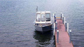 Small boat tied to narrow dock. A view of a small boat tied to a narrow dock Royalty Free Stock Photo