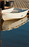 Small boat tied to a wooden dock and reflection Royalty Free Stock Images