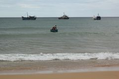 Small boat is trying to go to big boat on the sea at Phu Yen, VietNam - September 5,2018 royalty free stock image