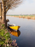 Small boat under a willow tree Stock Photos