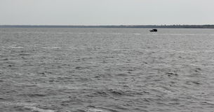 Small boat in the vastness of the sea Stock Photography