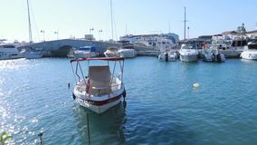 A small boat on the water in the Limassol marina with nice wave reflections on its hull. Cyprus stock footage