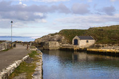 The small boathouse and slipway at Ballintoy harbor on the North Antrim Coast of Northern Ireland with its stone built boathouse o stock photography