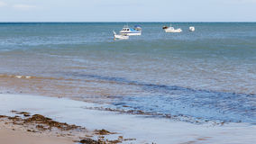 Small boats anchored just off shore. Royalty Free Stock Photo