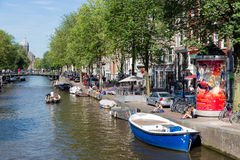 Small boats in canal with historic mansions in Amsterdam Royalty Free Stock Image