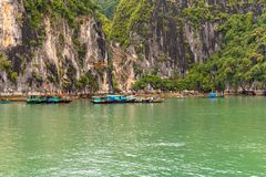 Small Boats form a Fishing Village in Hal Long Bay. Ha Long Bay, Vietnam -- March 24, 2016. Boats tied together at the base of huge rock formations form a Stock Photos