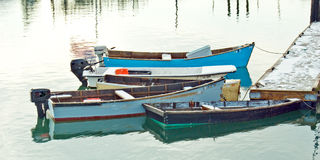Small boats in harbor. Small boats moored in a calm harbor early morning in winter Royalty Free Stock Images