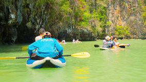 Small boats - kayaks are used for tourists entertainment. Inspection of ancient limestone cliff stock footage