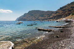 Small boats at lagoon of Tirassia island. Tirassia is a small island in caldera of Santorini island, Greece Stock Photography