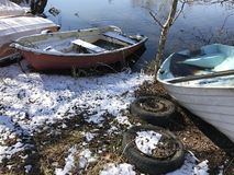 Small boats on land during winter. Old car tires royalty free stock photos