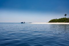 Small boats landing on beautiful white sandy beach of deserted tropical island royalty free stock photos