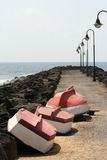 Small Boats in a Line. Group of 4 small rowing boats pulled up on a breakwater for the winter Royalty Free Stock Photo