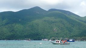 Small boats lying in tranquil bay in front of big mountain landscape stock video