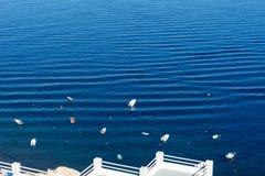 Small boats in the Mediterranean Sea off the island of Santorini Stock Image