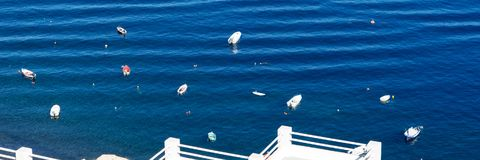 Small boats in the Mediterranean Sea off the island of Santorini Royalty Free Stock Photo
