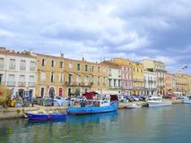 Small boats moored by waterfront houses. In the city of Sete in France stock photography