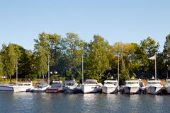 Small boats in one line near trees Stock Photography