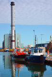 Small boats and power station in background Stock Photography