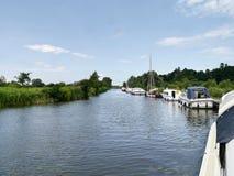 Small boats at riverside moorings on sunny day Royalty Free Stock Photos