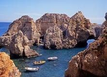 Small boats in rocky cove, Ponta da Piedade. Stock Photography