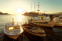 Small boats and a sailboat moored in the harbor of a town Postira - Croatia, island Brac Stock Photo
