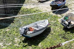 Small boats suspended on the ship in the smallest port of France, Port Racine, Cotentin peninsula. PORT RACINE, CHERBOURG, NORMANDY, FRANCE - JUNE CIRCA, 2018 royalty free stock photo